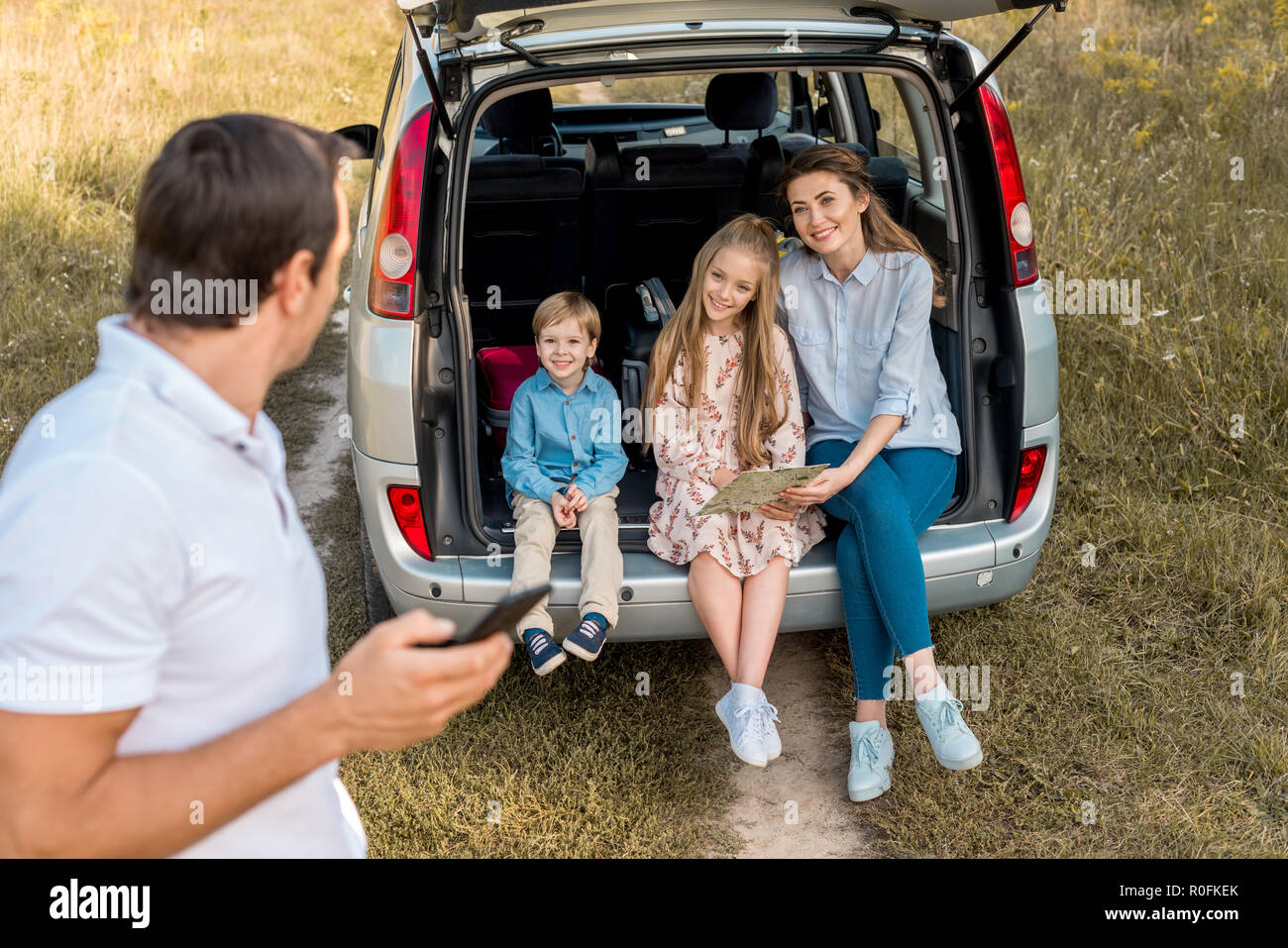 man using smartphone while his family sitting in car trunk in field - Stock Image