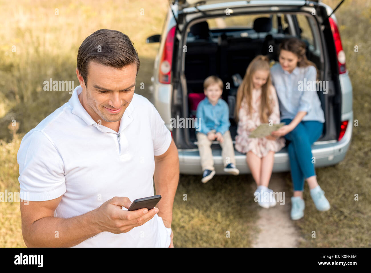 happy man using smartphone while his family sitting in car trunk in field - Stock Image