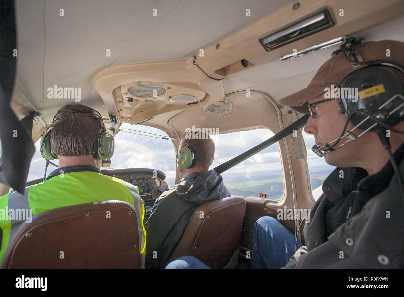 Pilot, co pilot, and passenger flying in a Piper PA-28 Cherokee light aircraft out of Northumbria Flying School, Newcastle Airport, Tyne and Wear, UK - Stock Image