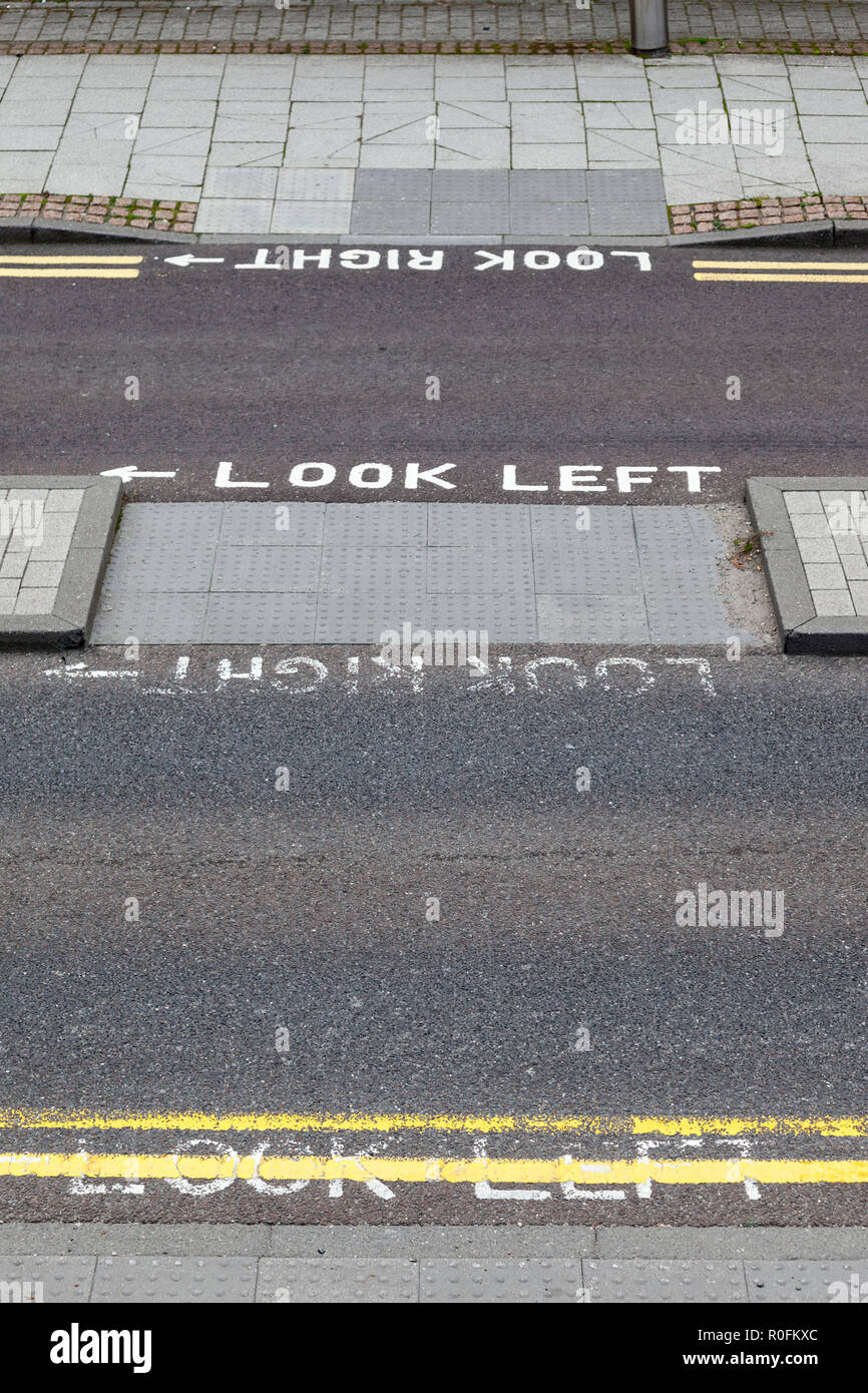 Markings on a pedestrian crossing over a road saying look left and look right, with a refuge between the two lanes, Gateshead, Tyne and Wear, UK - Stock Image