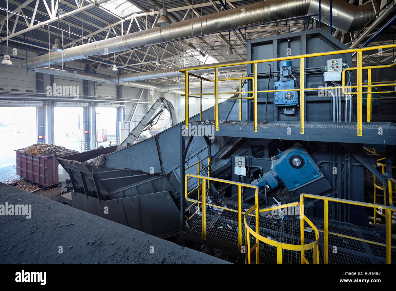 Refiner and chain-stepped conveyor equipment of modern waste recycling plant transports waste from receiving department to sorting, recycling and disp Stock Photo