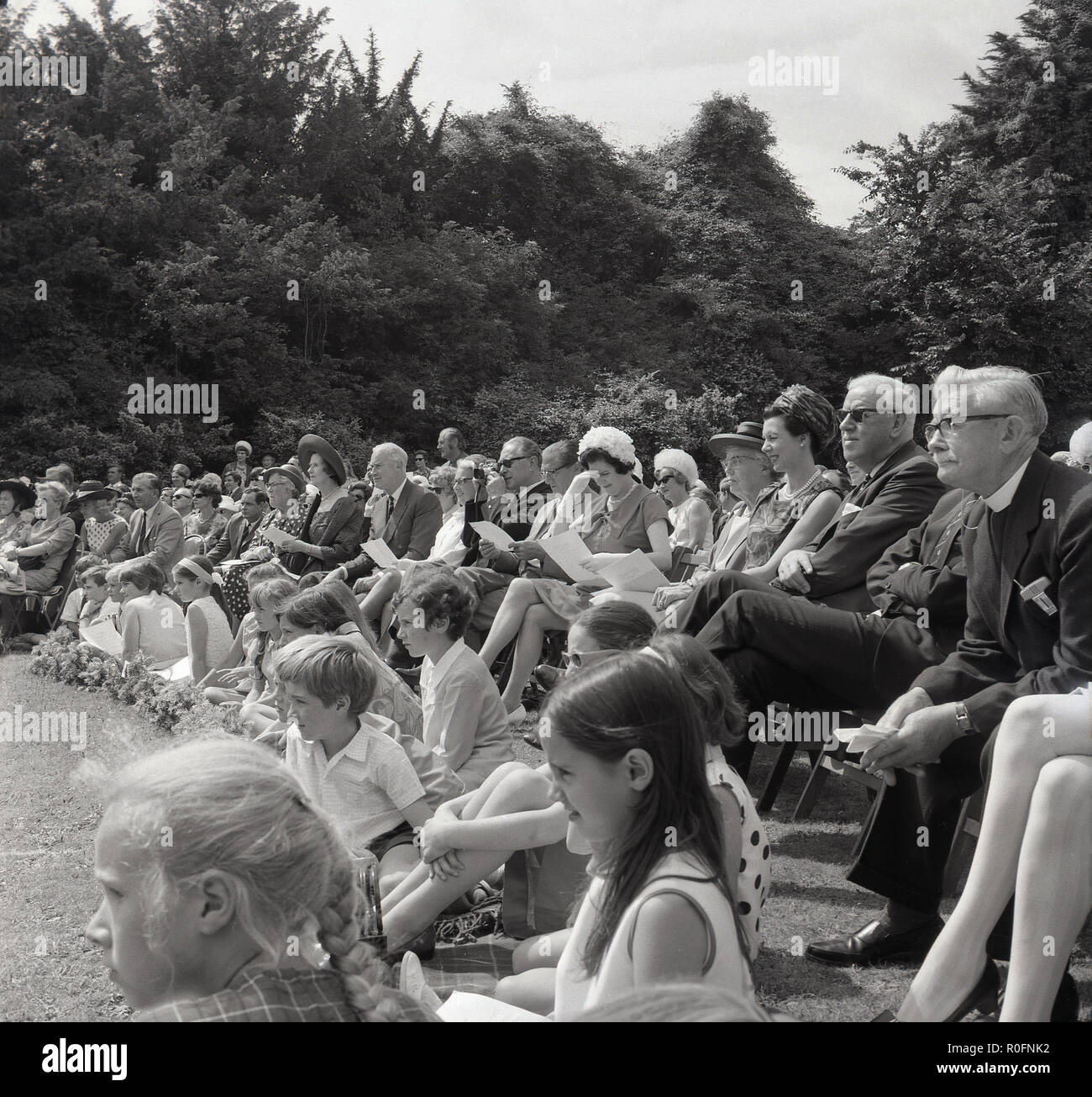 1967, picture shows a large group of spectators watching an event at the Tring Arts summer festival, Tring, Hertfordshire, England, UK. The festival was outdoors at Tring Park, the school for the Performing Arts, the home of the Arts Educational School. - Stock Image
