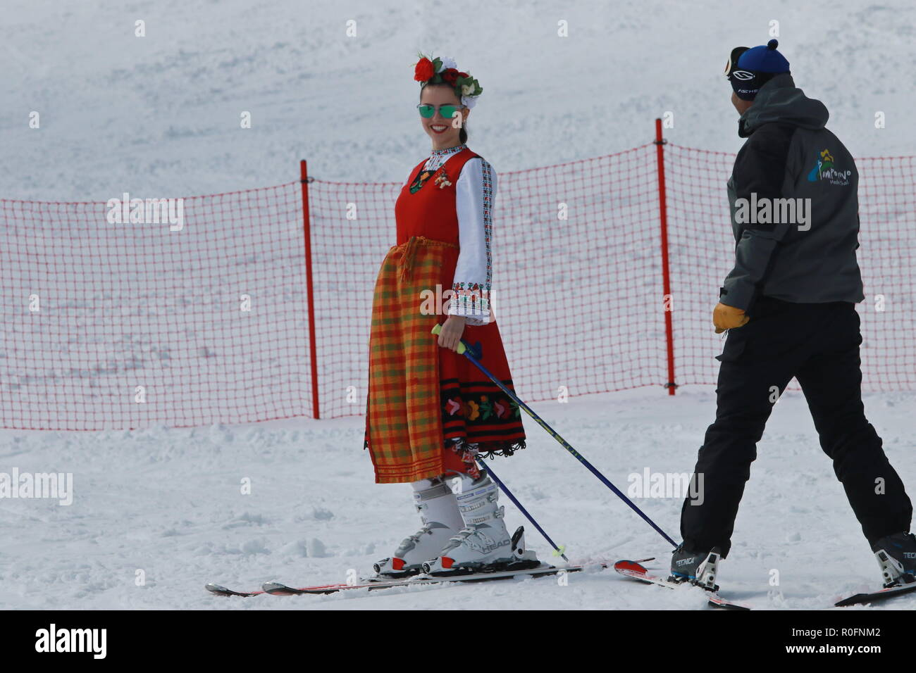 Skiing with Bulgarian flags at Pamporovo ski resort, Bulgaria. People dressed with traditional Bulgarian clothes skiing with the national flag. - Stock Image