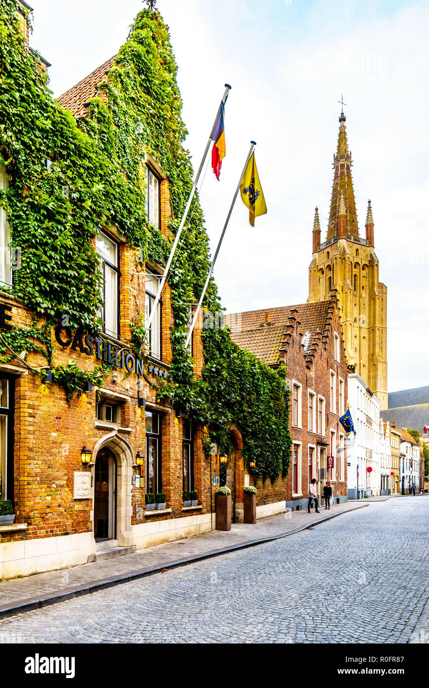 One of the many cobblestone streets in the heart of Bruges, Belgium with the tower of the Church of Our Lady in the backgound - Stock Image