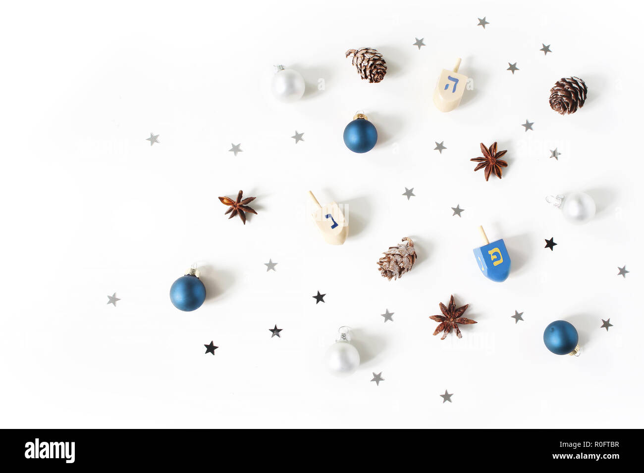 Hanukkah styled stock composition. Decorative pattern. Wooden dreidel toys, larch cones, anise and silver confetti stars decoration on white background. Flat lay, top view. Jewish design. - Stock Image