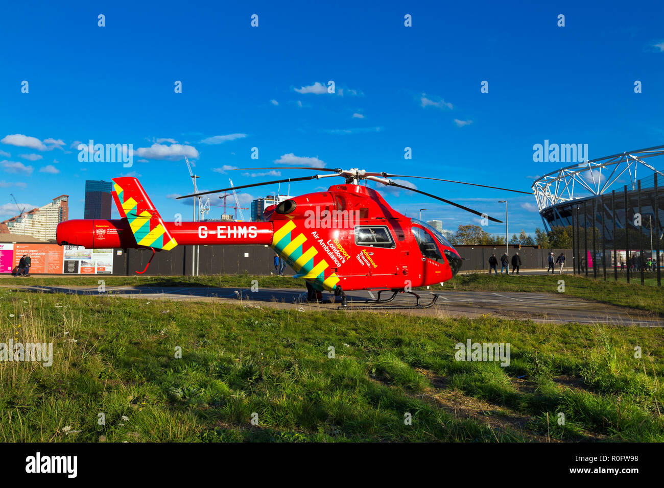 London Air Ambulance red helicopter stationed by the stadium in the Queen Elizabeth Olympic Park, London, UK - Stock Image