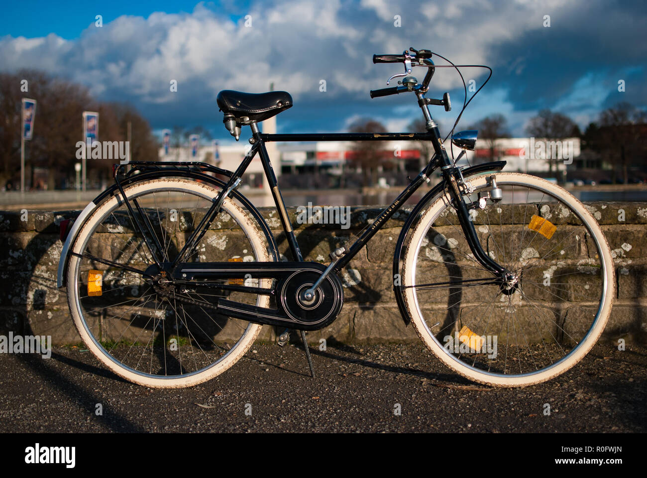 An old vintage bike in front of a stone wall and the cloudy blue sky - Stock Image
