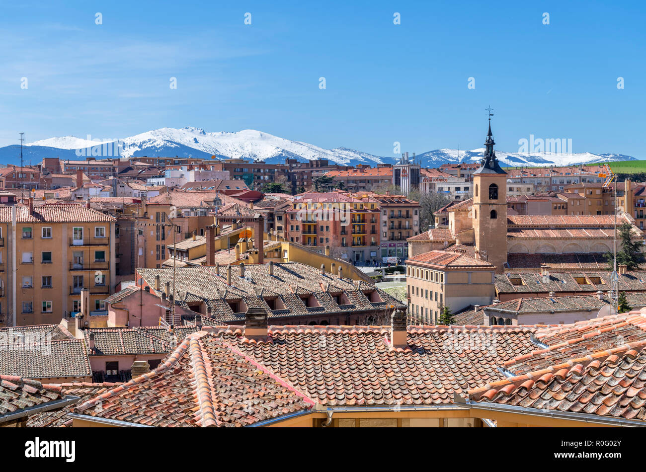 View over the rooftops of the old town towards snow-capped mountains, Segovia, Castilla y Leon, Spain - Stock Image