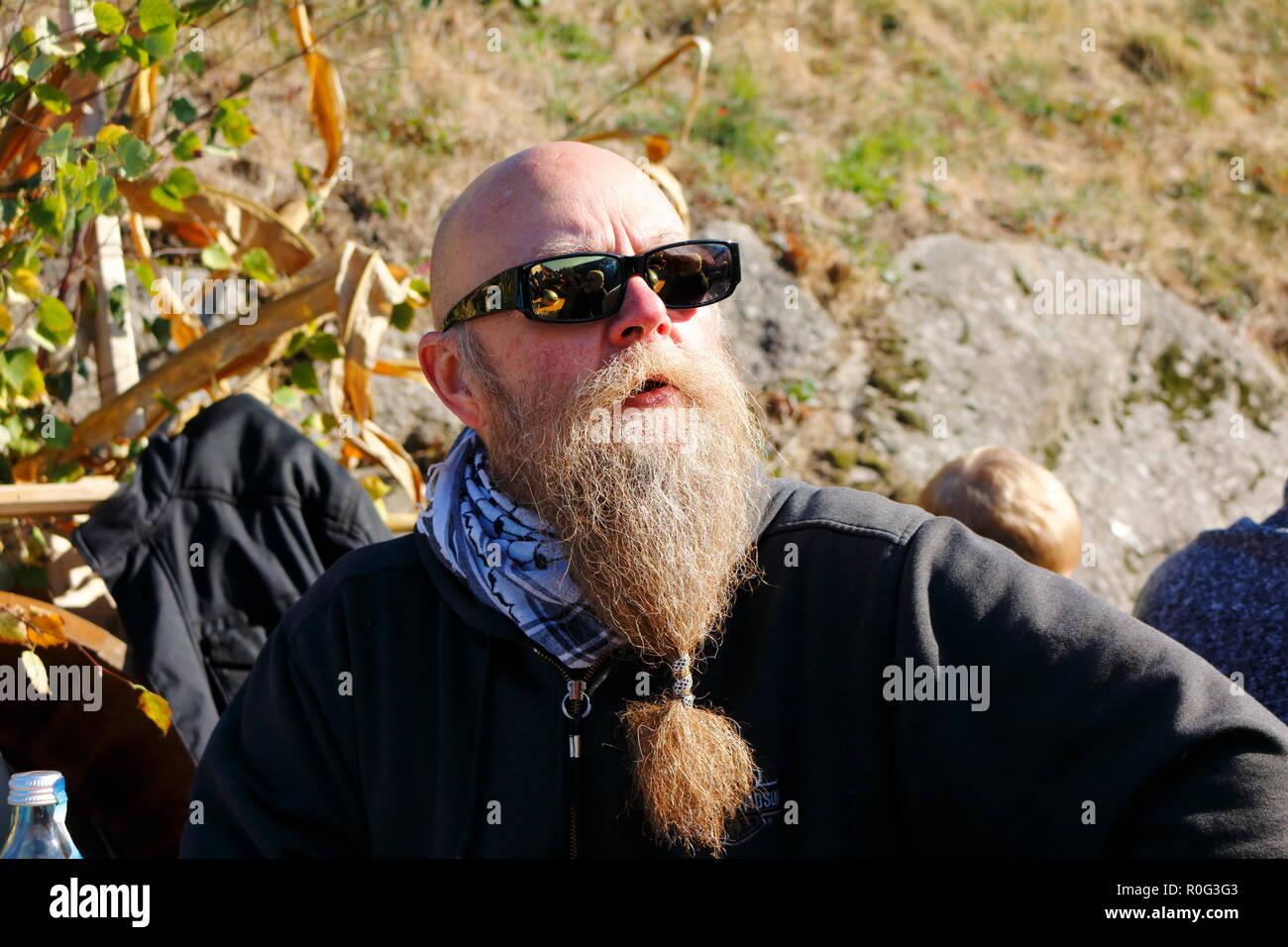 Mann mit langem Bart lächelt, und genießt die letzten Sonnenstrahlen im Herbst beim Erntedankfest - Stock Image