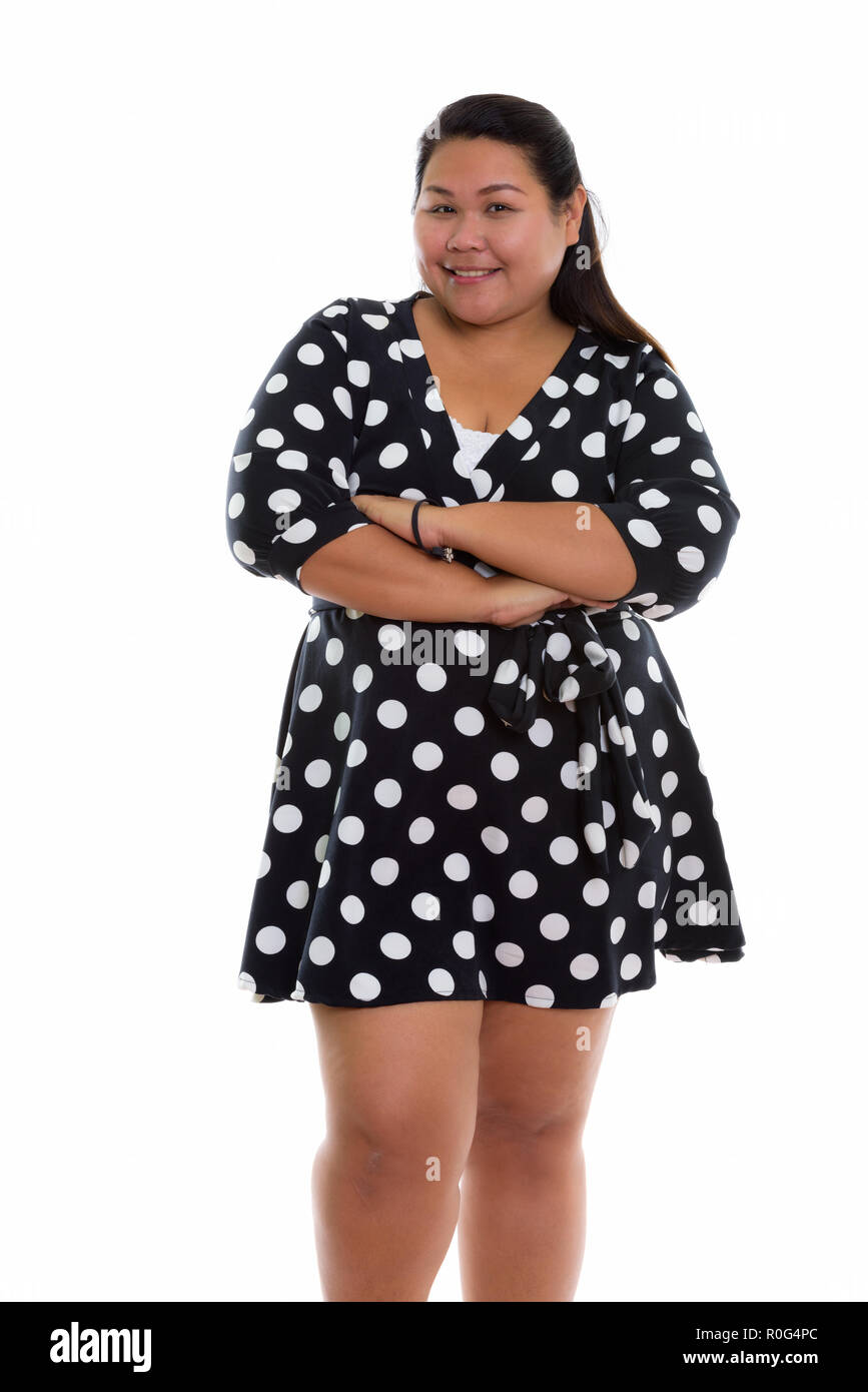 Studio shot of young happy fat Asian woman smiling and standing  Stock Photo