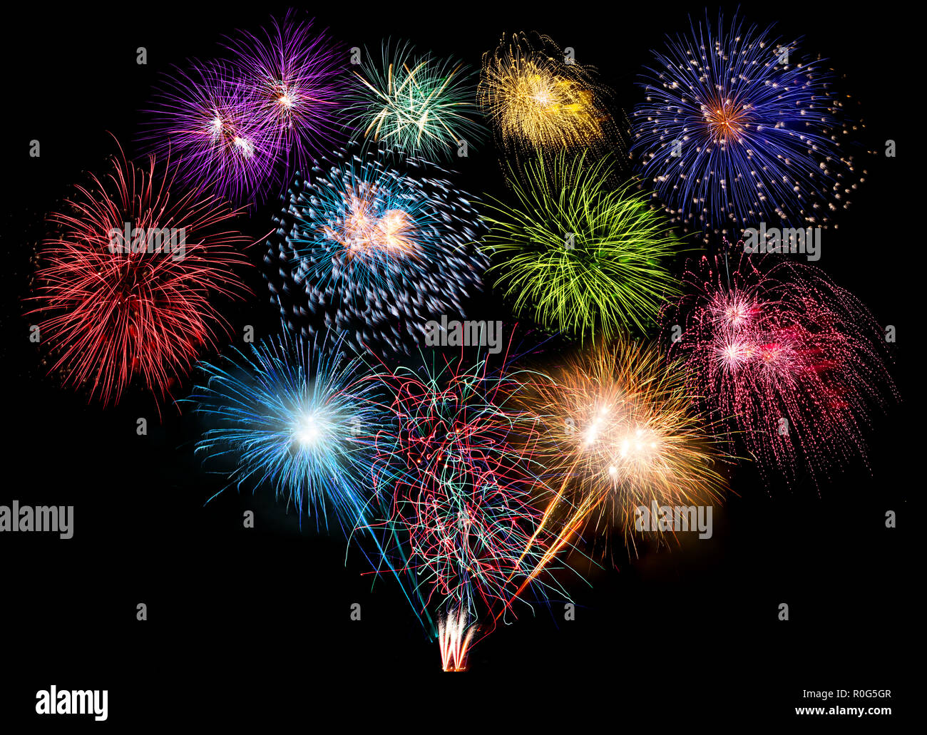 colorful fireworks display and bright sparkler pyrotechnic happy new year sylvester concept on black blue background - Stock Image