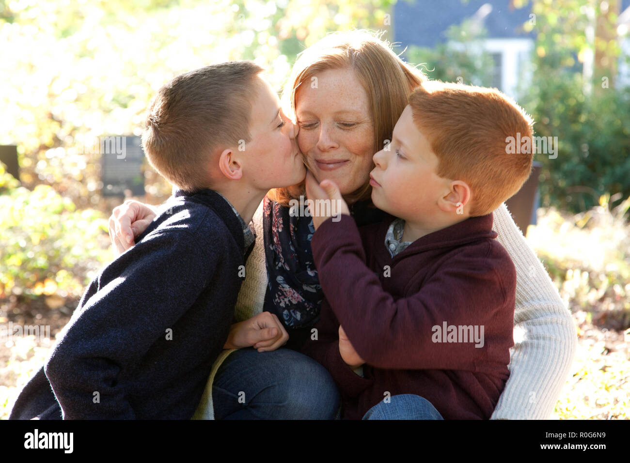 A red haired mother smiles peacefully as her two sons give her a gentle affectionate kiss - Stock Image