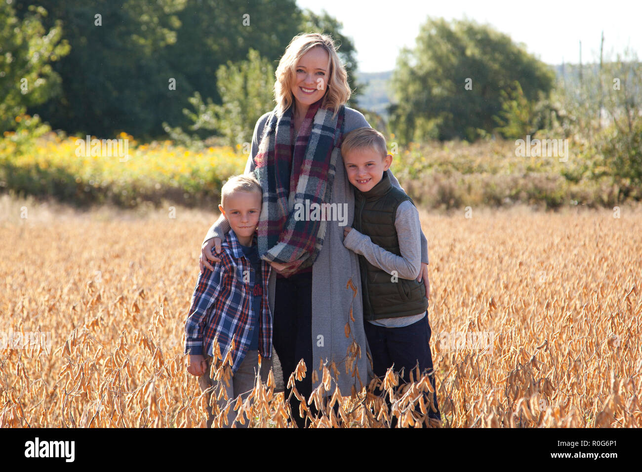 A beautiful smiling mom puts her arms around her two sweet sons, outside in a field - Stock Image