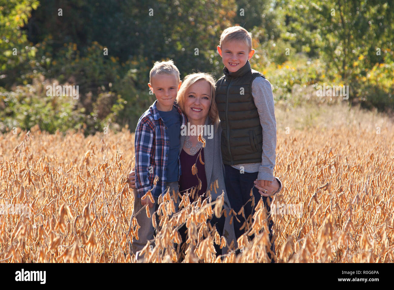 Beautiful blond mother crouches outside on an autumn day with her handsome sons - Stock Image