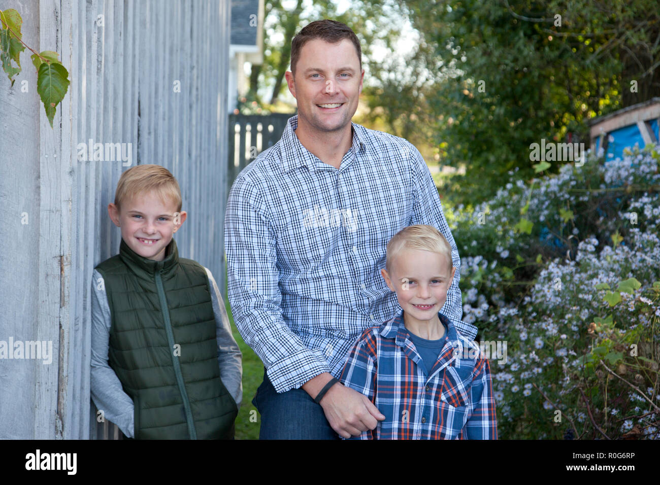 Smiling trio of three blond guys, a father and his two sweet sons - Stock Image