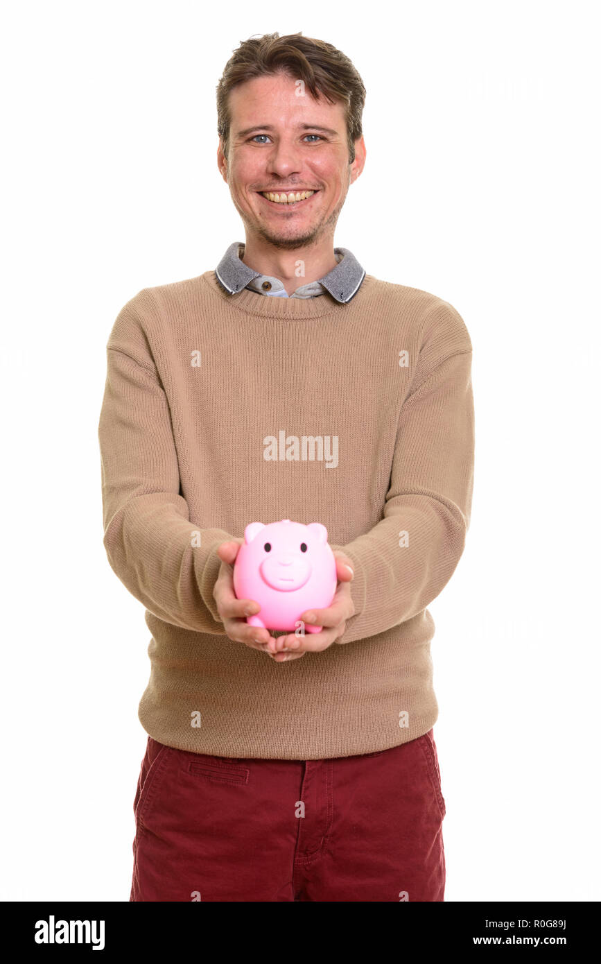 Happy Caucasian man holding piggy bank while smiling - Stock Image
