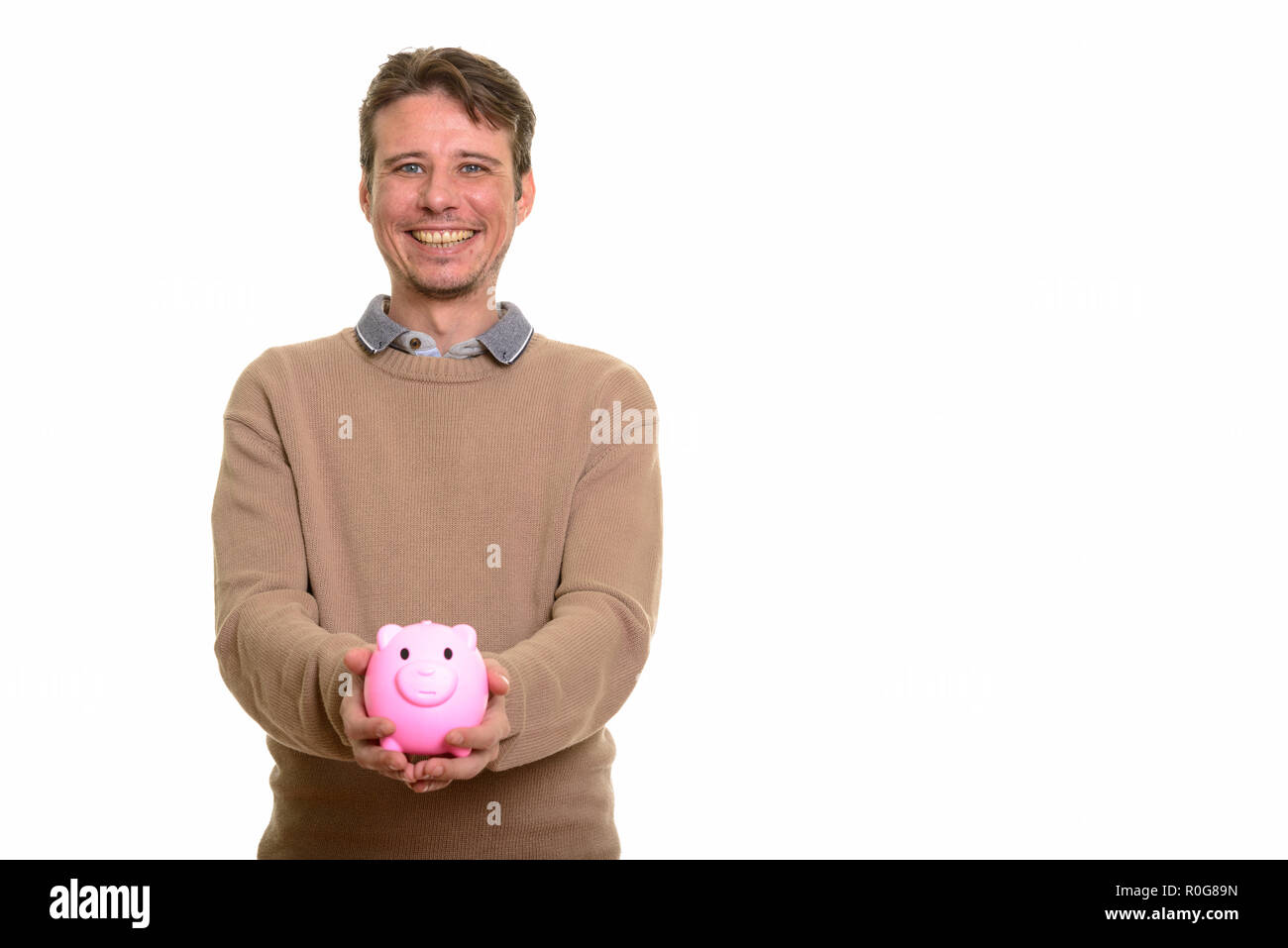 Happy Caucasian man holding piggy bank and looking at camera - Stock Image
