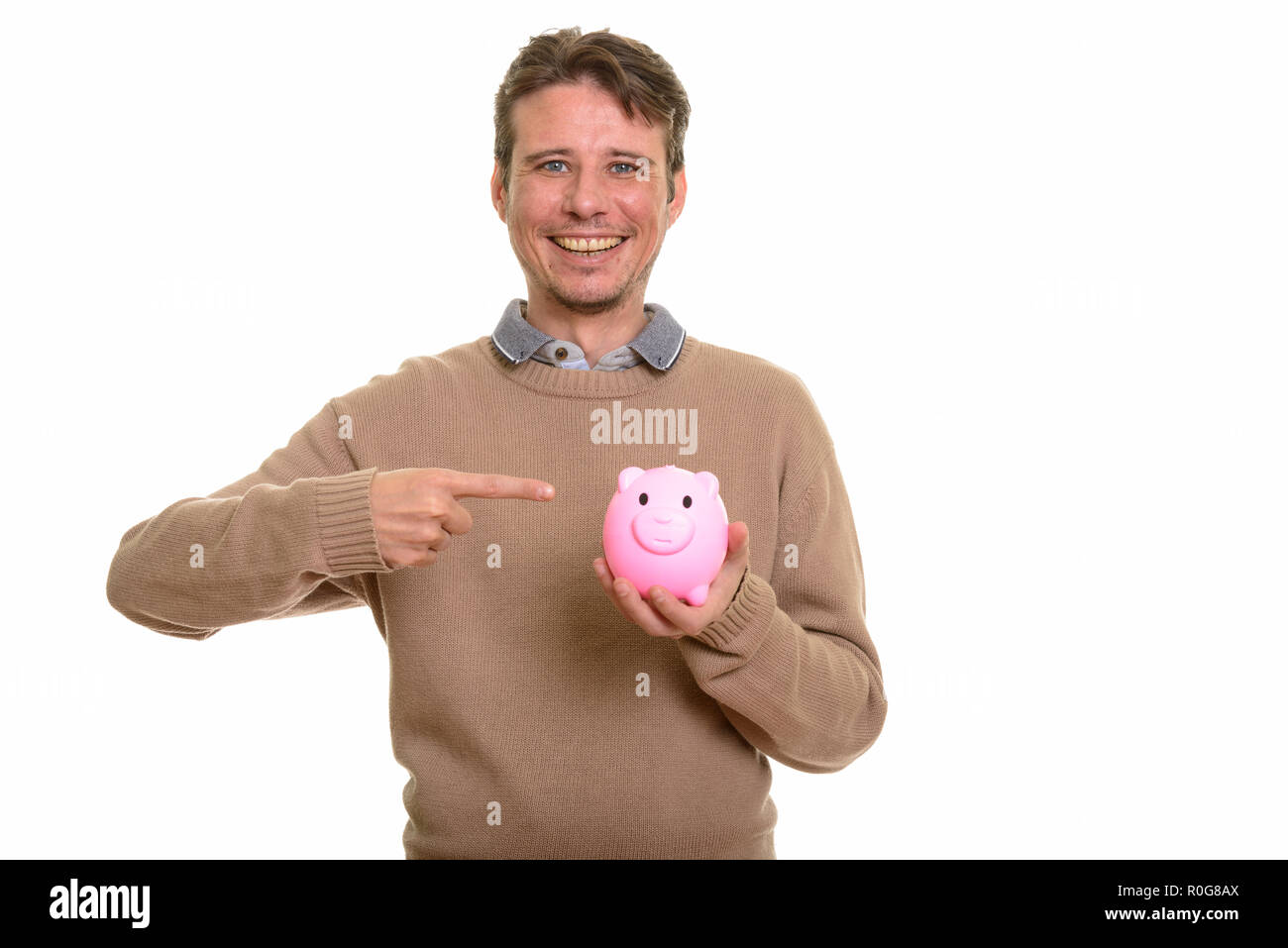 Happy Caucasian man holding piggy bank while pointing finger  - Stock Image
