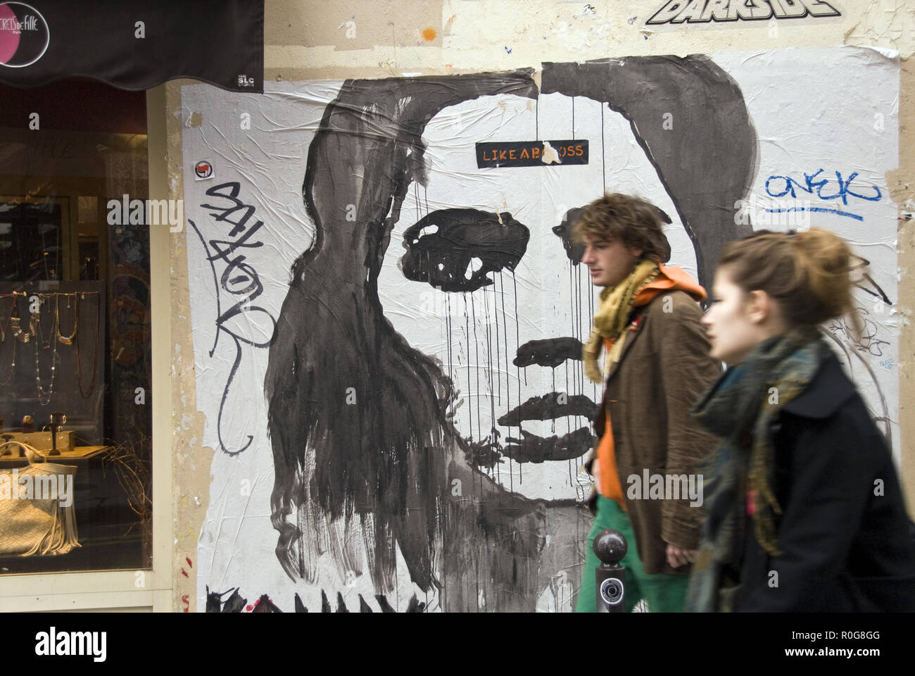 University students walk past a poster pasted to a wall in the Latin Quarter, near the Sorbonne, Paris, France. - Stock Image
