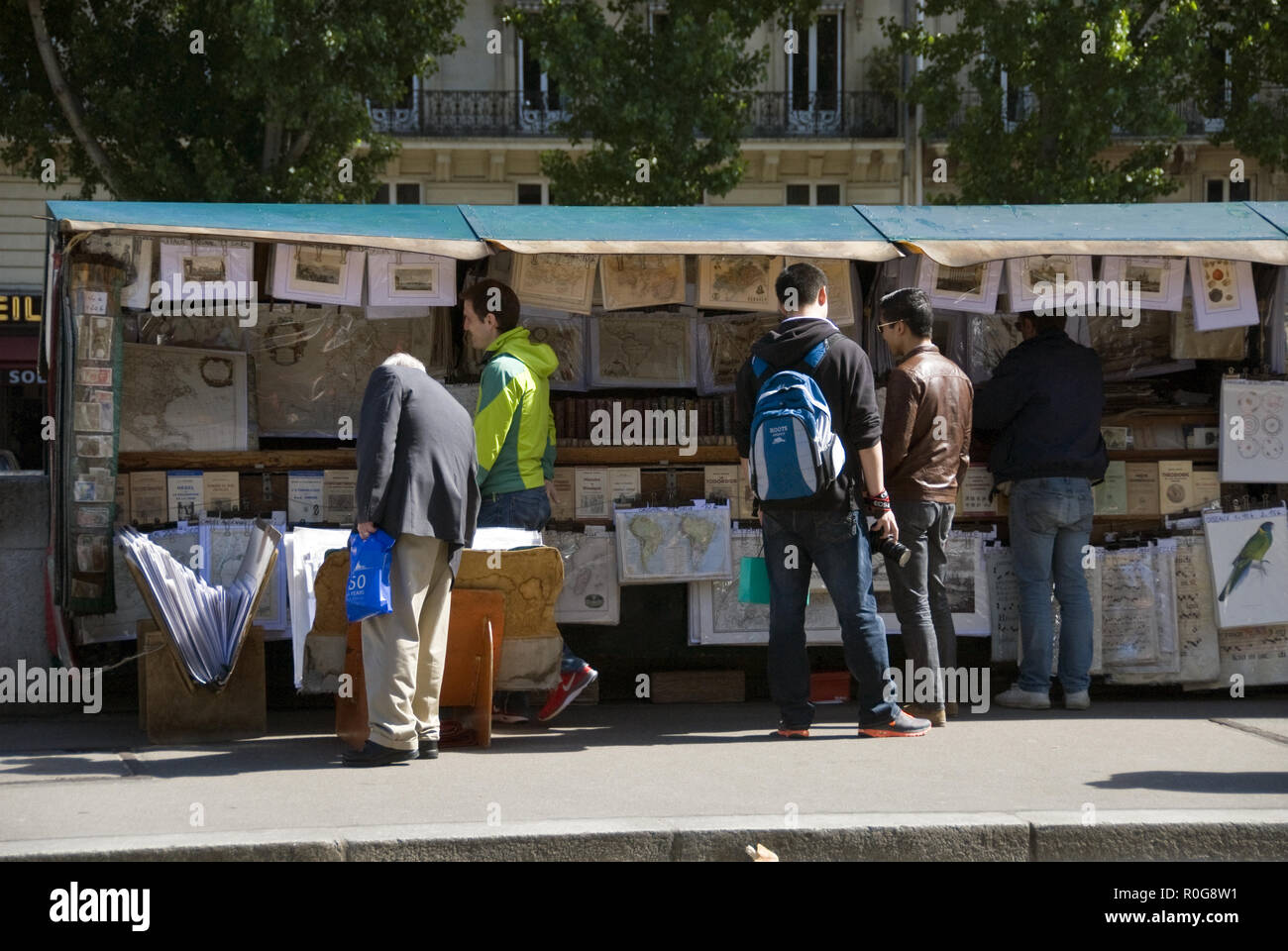 Shoppers peruse antique books, prints and maps at a book stall on the Seine river embankment, Paris, France. - Stock Image
