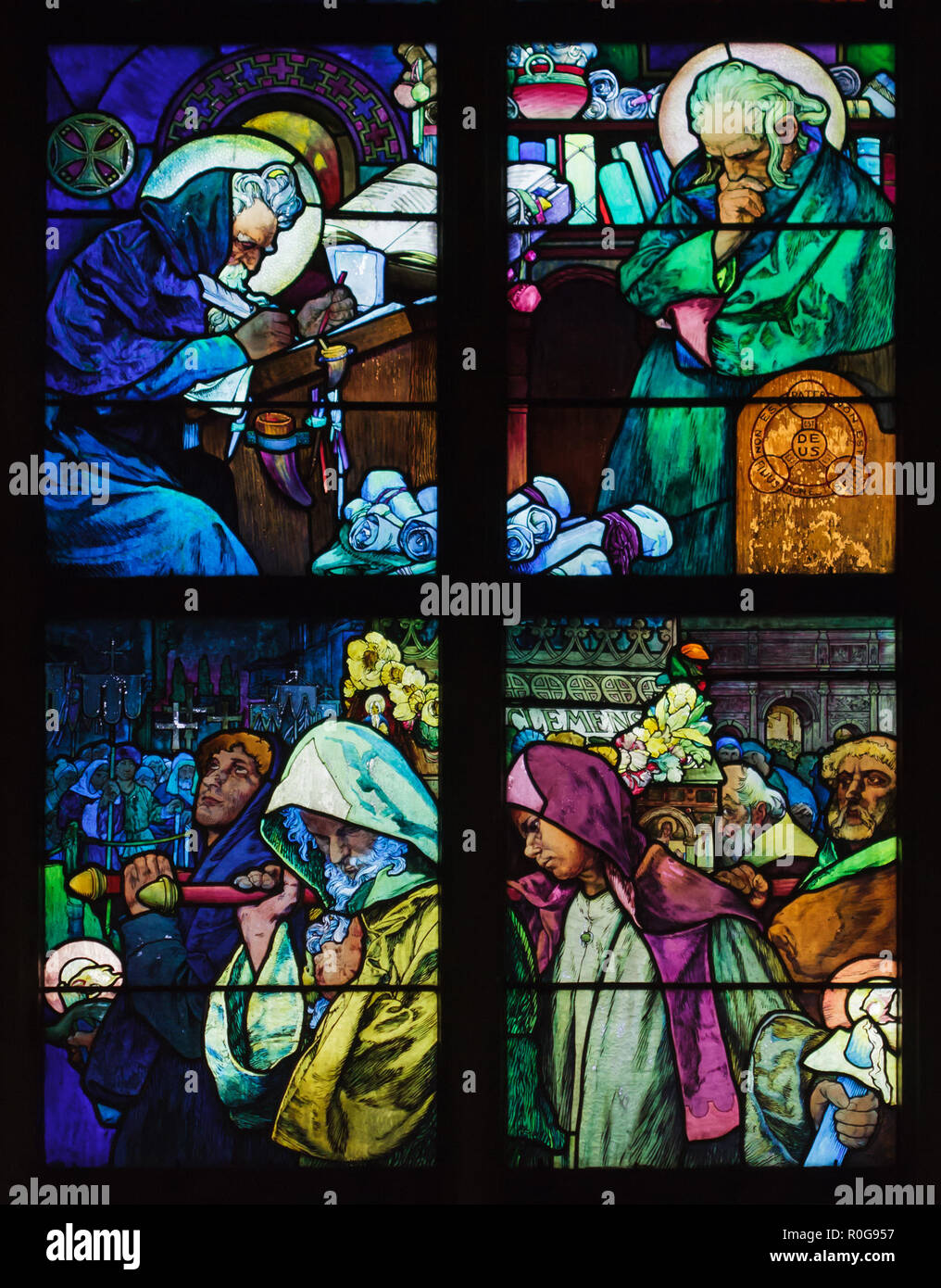 Detail of the stained-glass window designed by Czech Art Nouveau artist Alfons Mucha in Saint Vitus' Cathedral in the Prague Castle in Prague, Czech Republic. The scenes from the life of Saints Cyril and Methodius are depicted in the stained-glass window from top to bottom: Saints Cyril and Methodius invent Glagolitic alphabet for Slavonic language and translate the Bible to Slavonic language; Saints Cyril and Methodius transfer the relics of Saint Pope Clement I from Crimea to Rome. - Stock Image