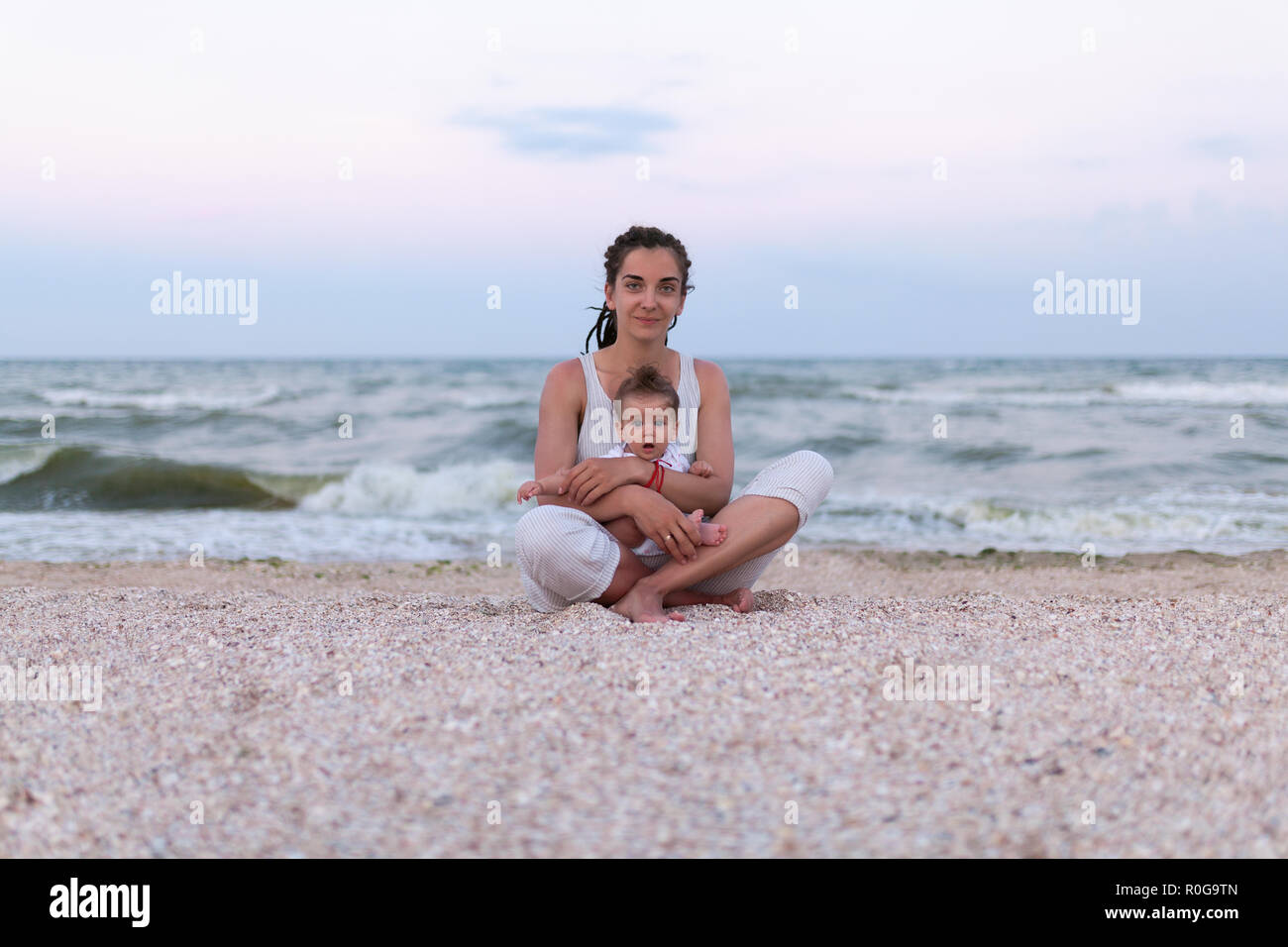 Happy family mother and child daughter doing yoga, meditate in lotus position on beach at sunset Happy family concept. Mother like friend - Stock Image