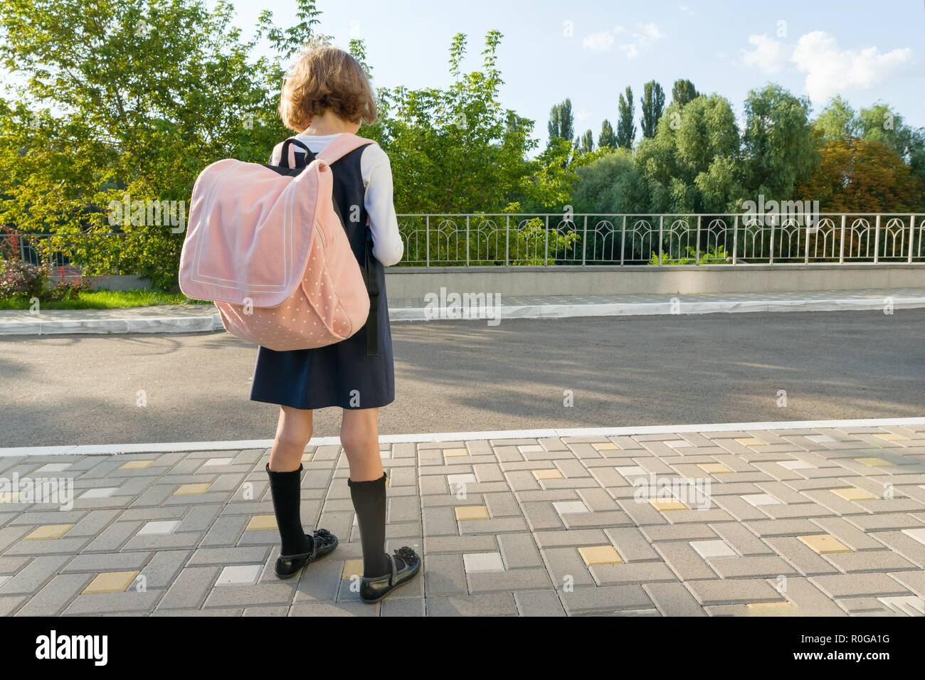 Outdoor portrait of a small student, girl with glasses, uniform with backpack. School, education, knowledge and children. Back view, copy space - Stock Image