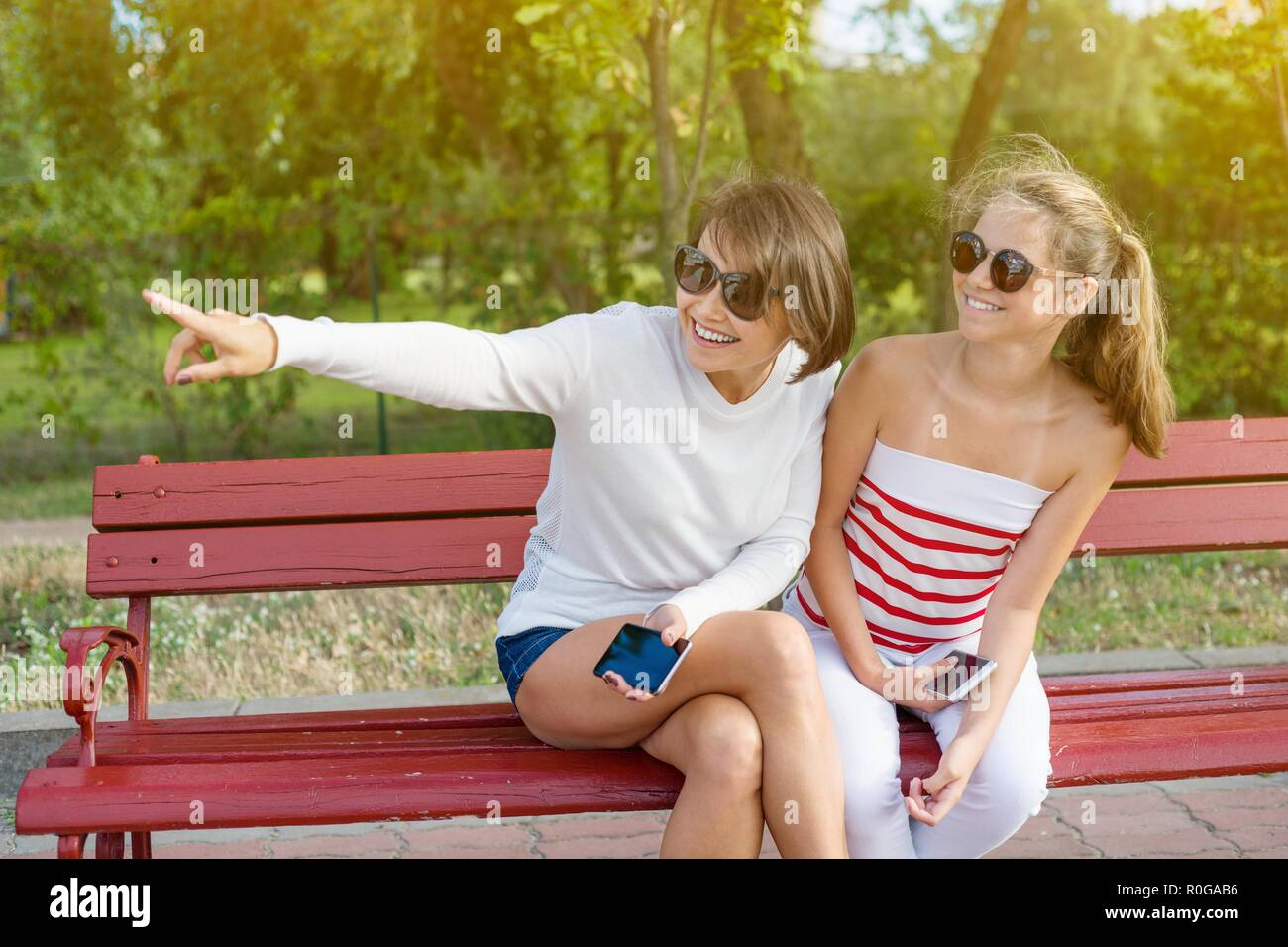 Communication between parent and child. Mom and daughter teenager talking and laughing while sitting on the bench in the park Stock Photo