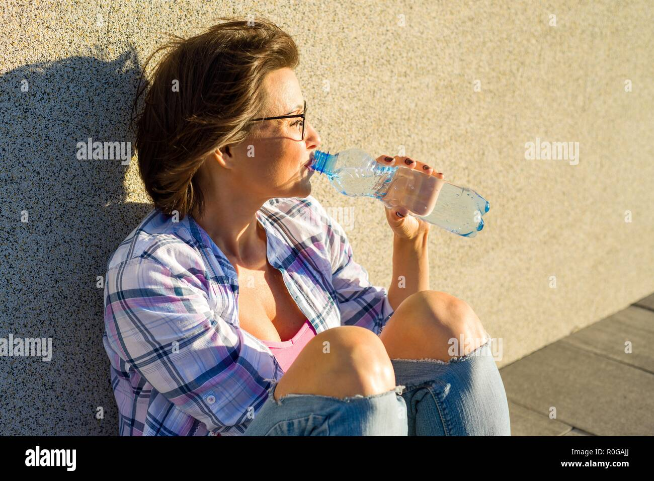 Adult woman with glasses is drinking water from bottle on hot summer day. - Stock Image