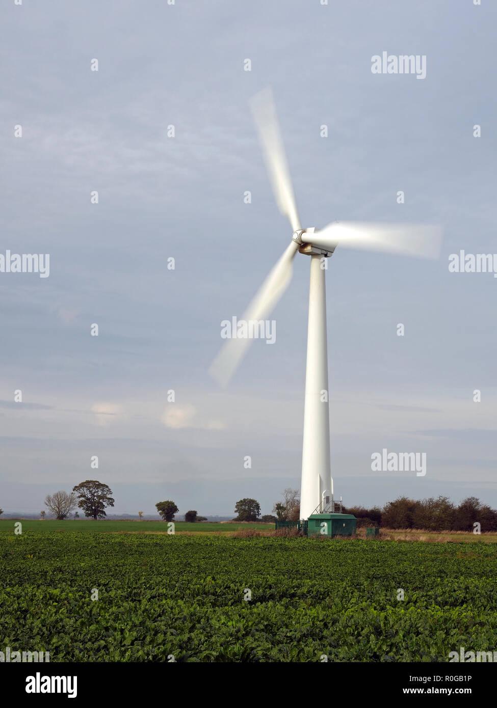 Onshore wind turbines on farmland at Somerton near the Norfolk coast spinning in a light autumn breeze. Stock Photo