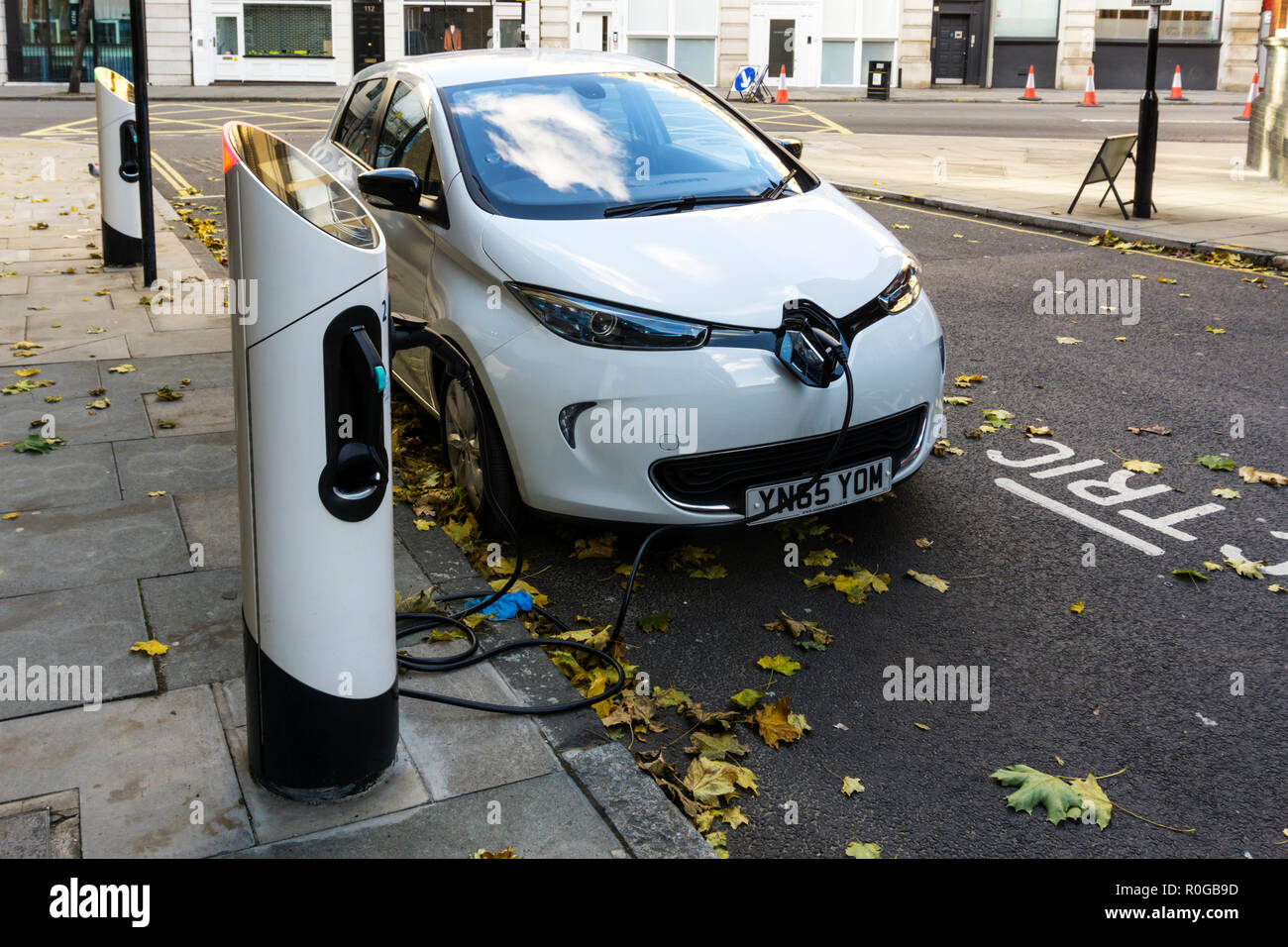 White Renault Zoe Dynamique NAV electric car charging at kerbside charging point. Stock Photo