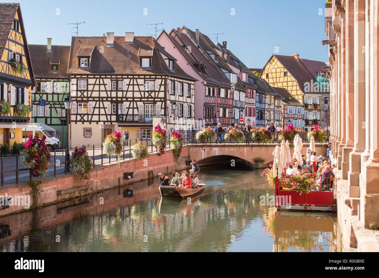 Colmar boat tour passing La Terrace Du Marche restaurant and colourful timber framed houses in the Fishmongers District, Colmar, Alsace, France - Stock Image