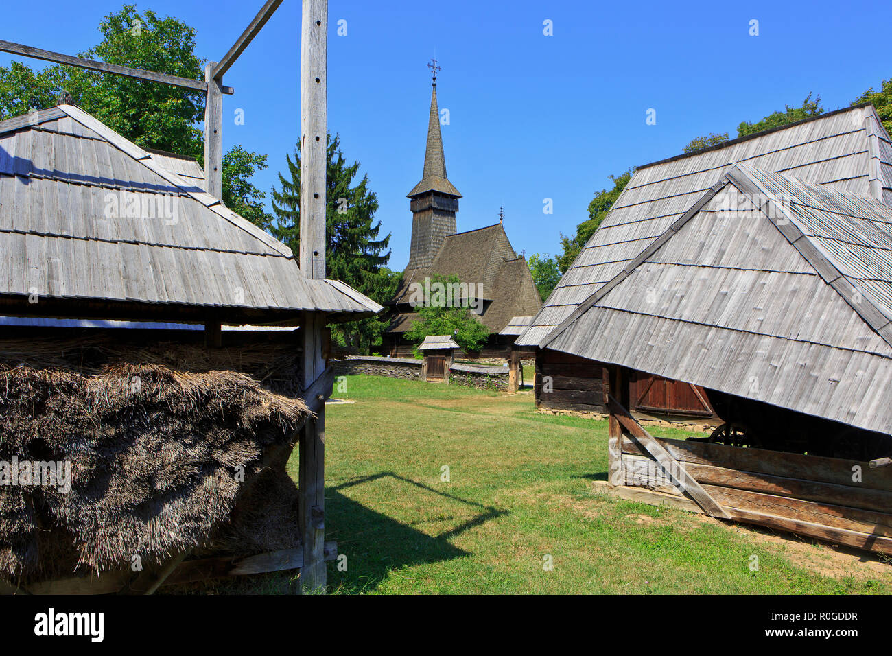 A beautiful wooden church amidst various traditional farmhouses at the Dimitrie Gusti National Village Museum in Bucharest, Romania - Stock Image