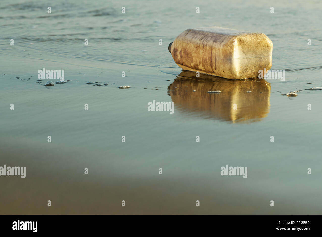 Dirty empty plastic container lying on its side where it washed out of the sea onto wet beach sand - Stock Image