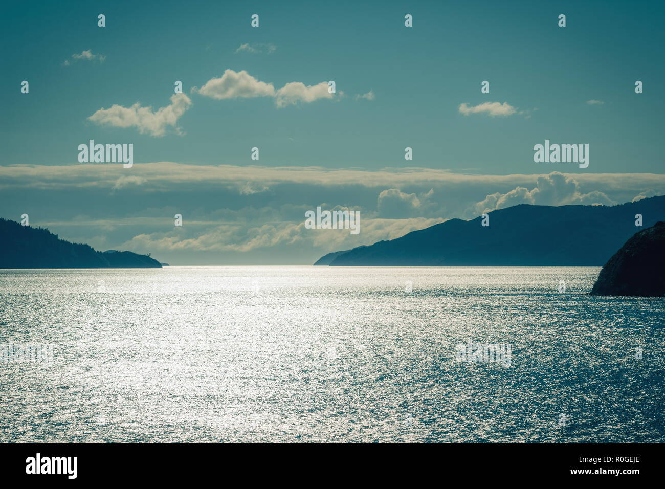 Background image of glistening water on the sea between islands of the Marlborough Sounds in New Zealand. - Stock Image