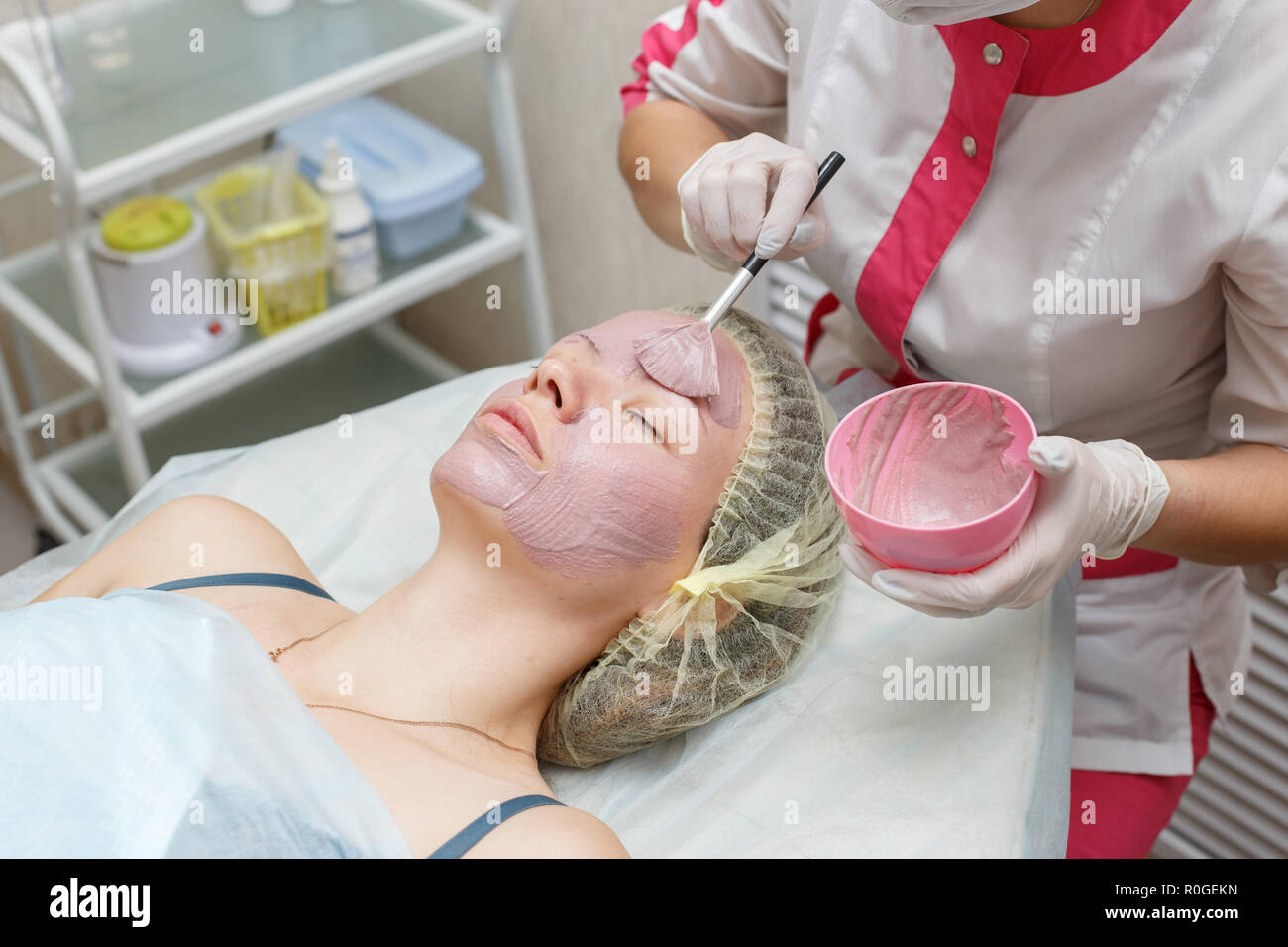 Woman getting pink face peeling mask in spa beauty salon by beautician - Stock Image
