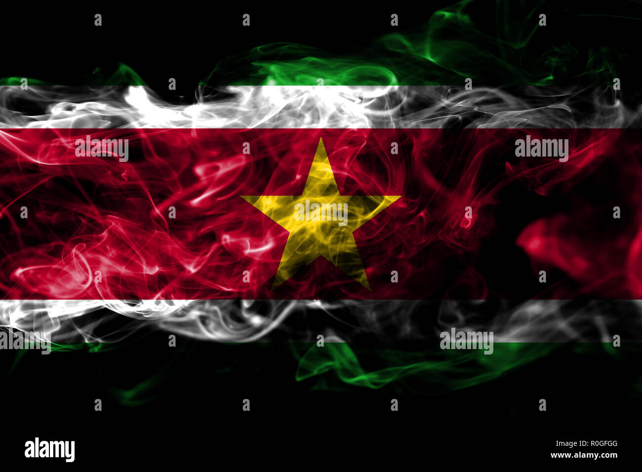 National flag of Suriname made from colored smoke isolated on black background. Abstract silky wave background - Stock Image