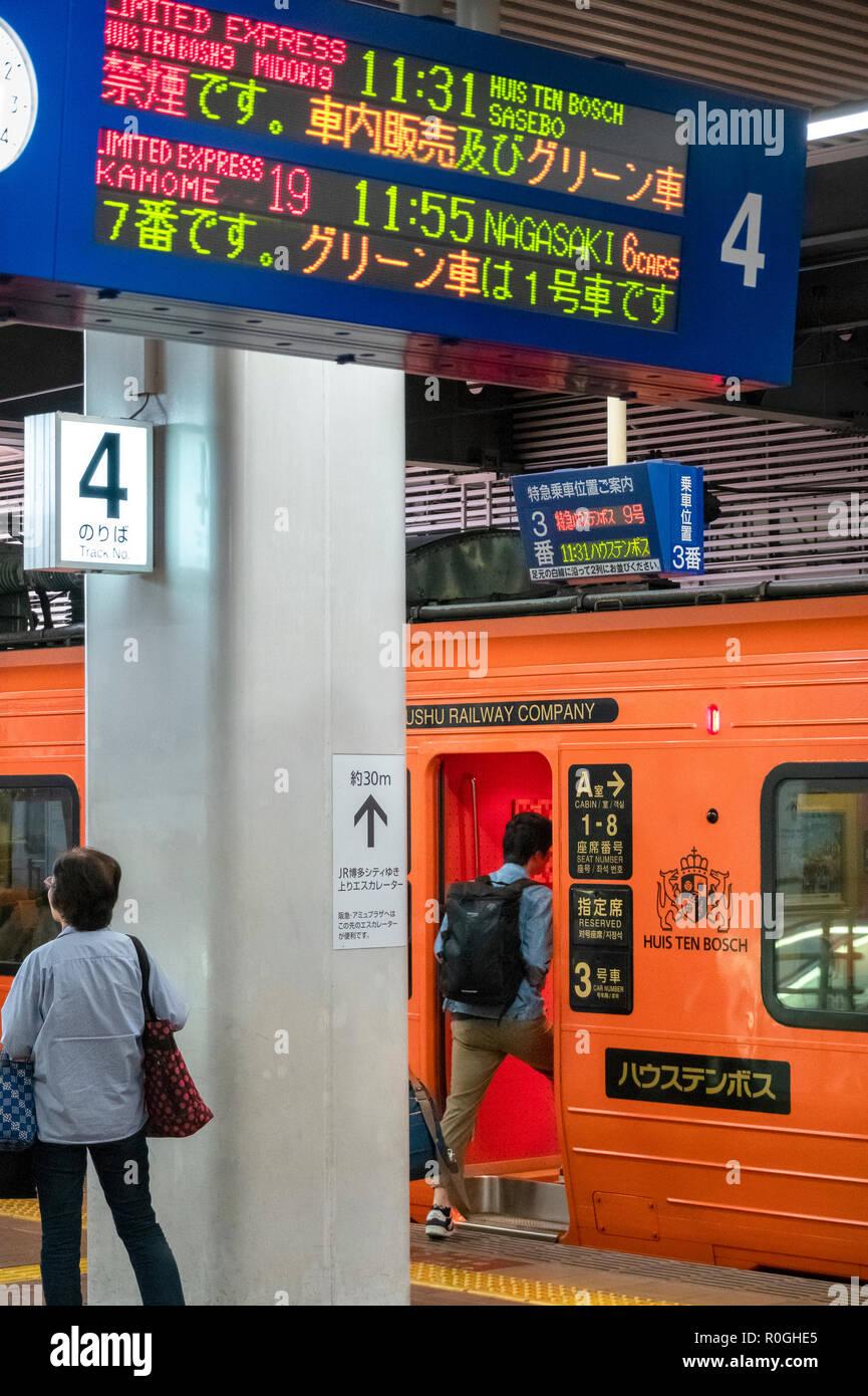A special orange JR Kyushu Rail train to Huis Ten Bosch theme park in Sasebo is about to depart from Fukuoka Hakata Station. - Stock Image