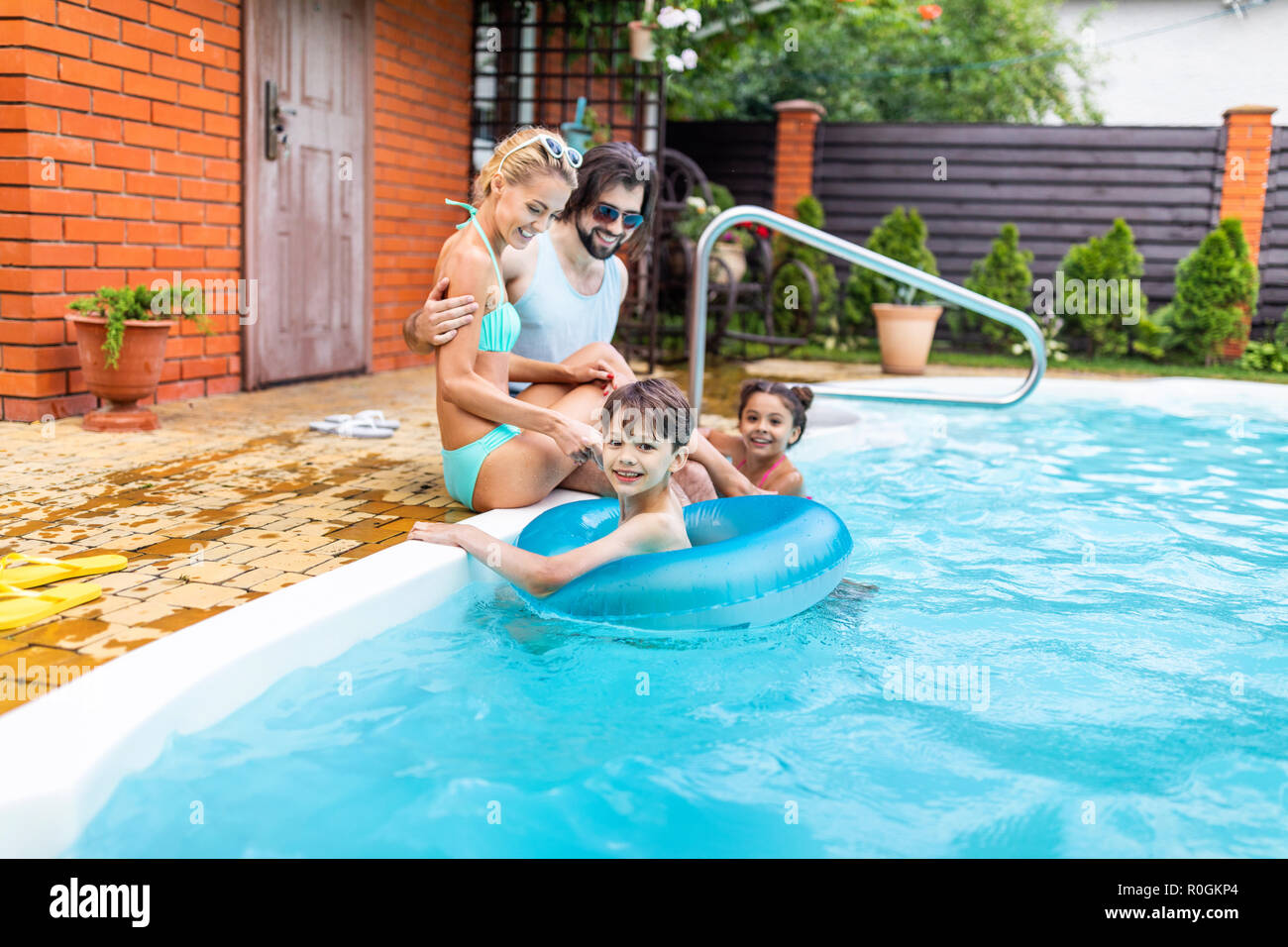 family spending time near swimming pool at countryside backyard on summer day - Stock Image