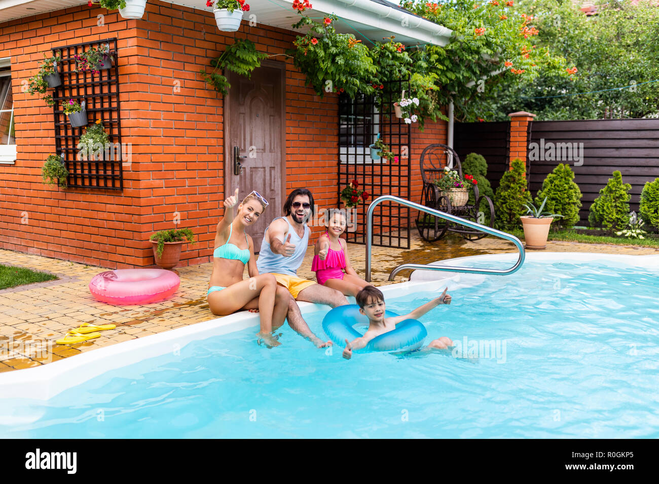 family showing thumbs up while spending time near swimming pool on summer day - Stock Image