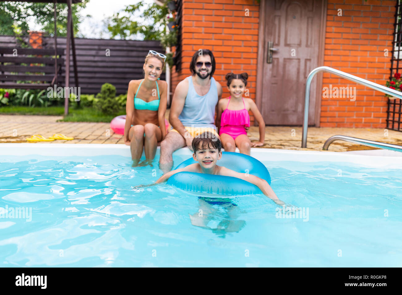 selective focus of happy family spending time near swimming pool at countryside backyard on summer day - Stock Image