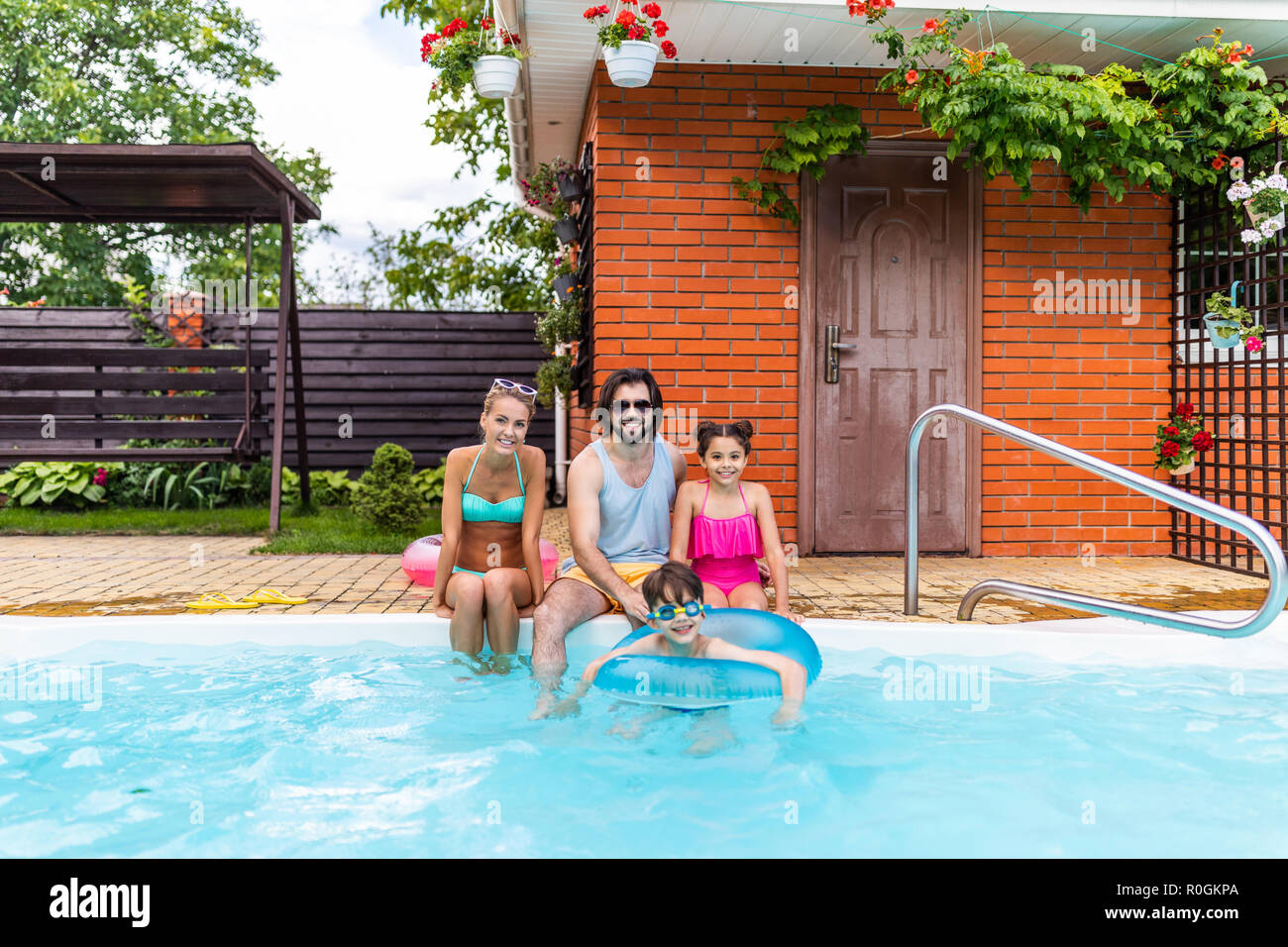 happy family spending time near swimming pool at countryside backyard on summer day - Stock Image