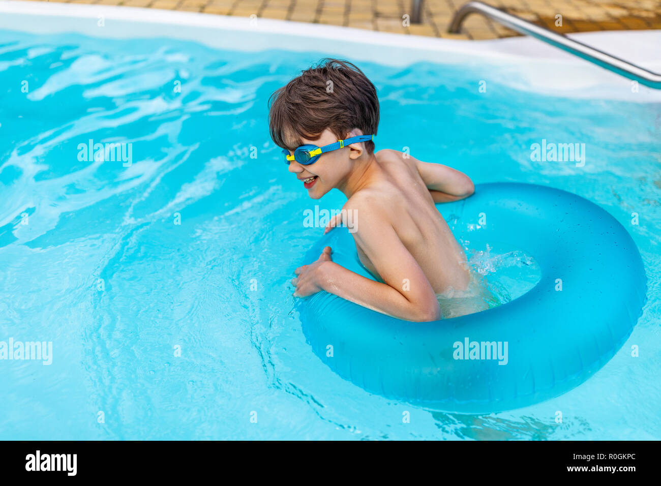 side view of happy boy in swimming glasses with inflatable ring swimming in swimming pool on summer day - Stock Image