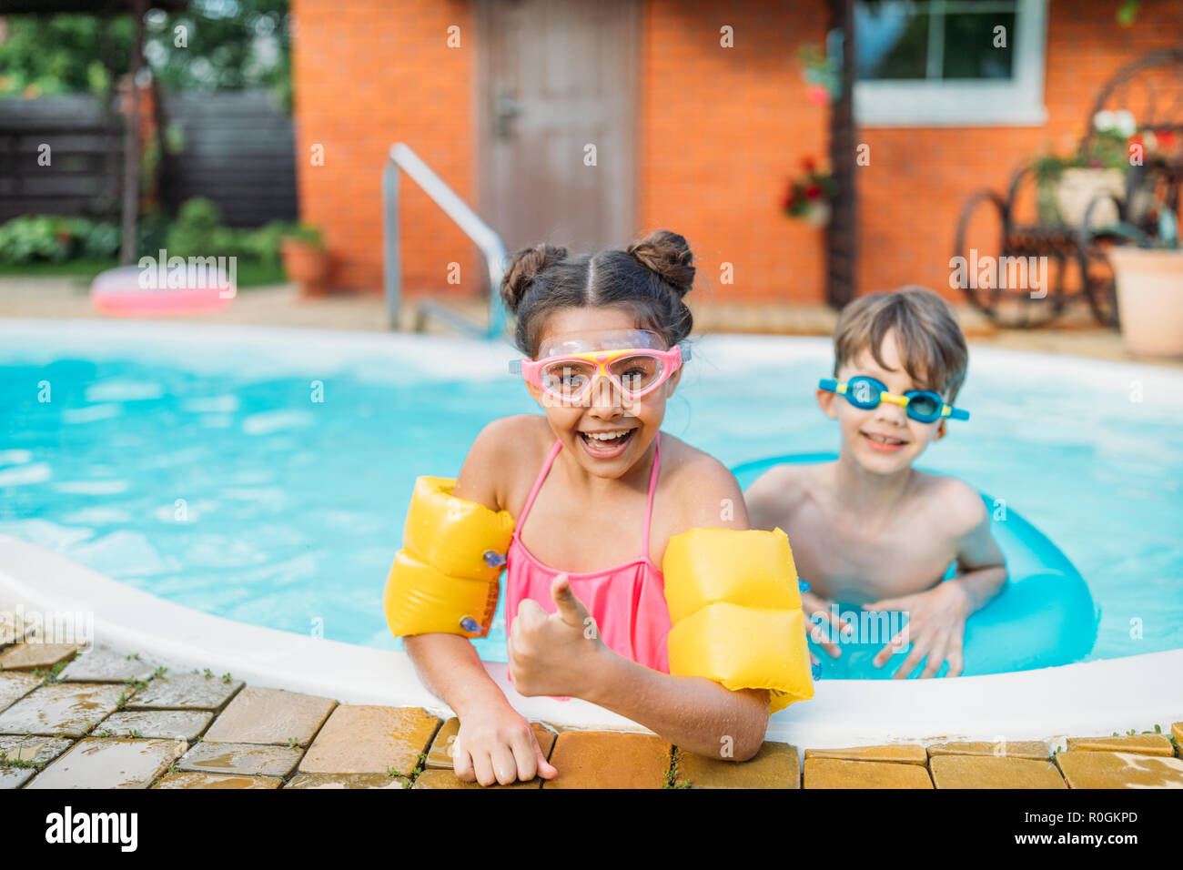 little siblings swimming in swimming pool together on summer day - Stock Image