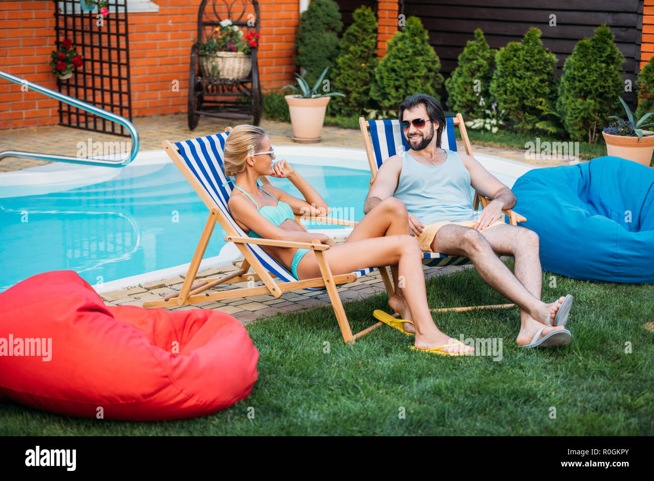 smiling couple on beach chairs spending time near swimming pool on backyard on summer day - Stock Image