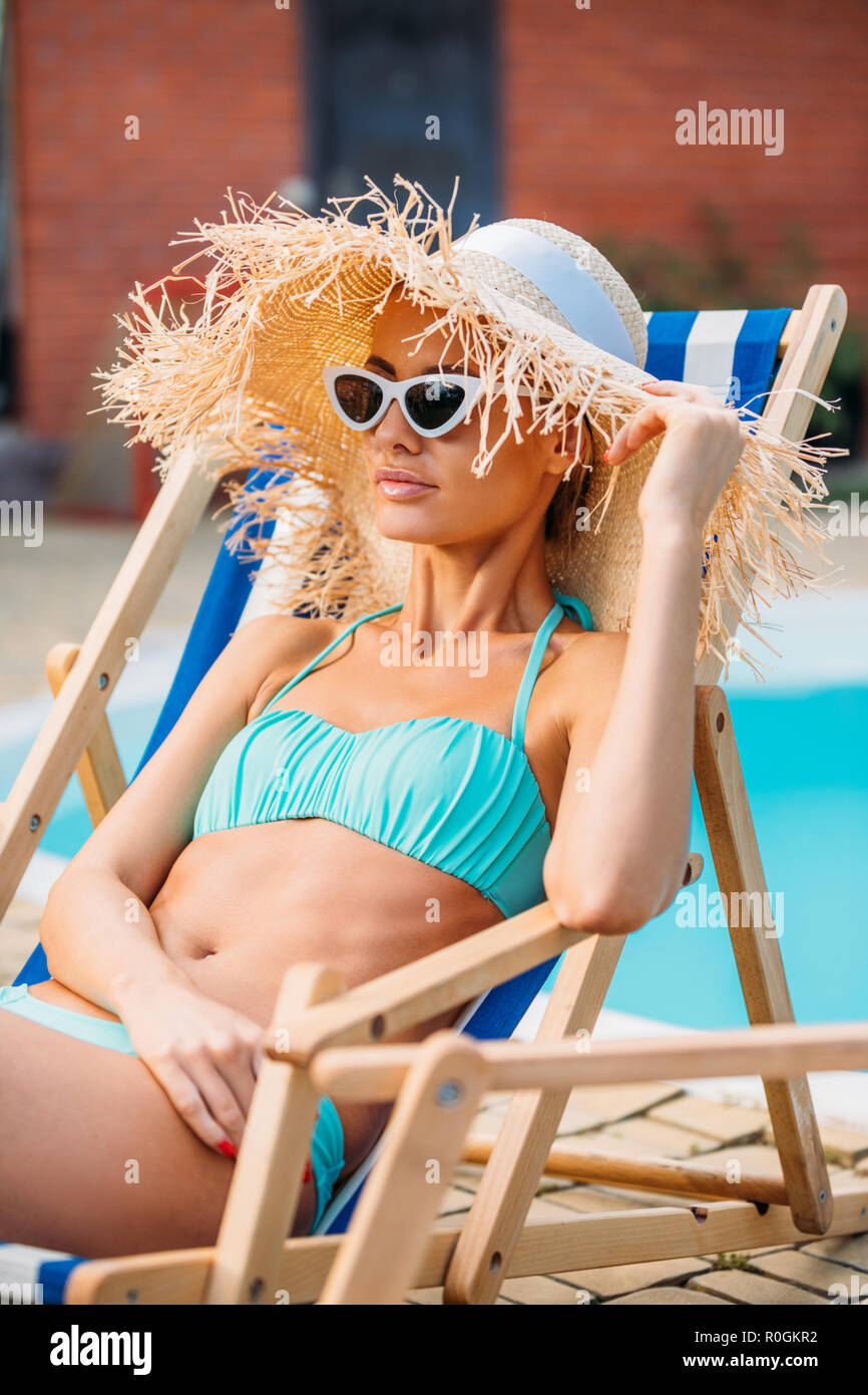 portrait of beautiful woman in straw hat and sunglasses resting on beach chair at swimming pool on summer day Stock Photo