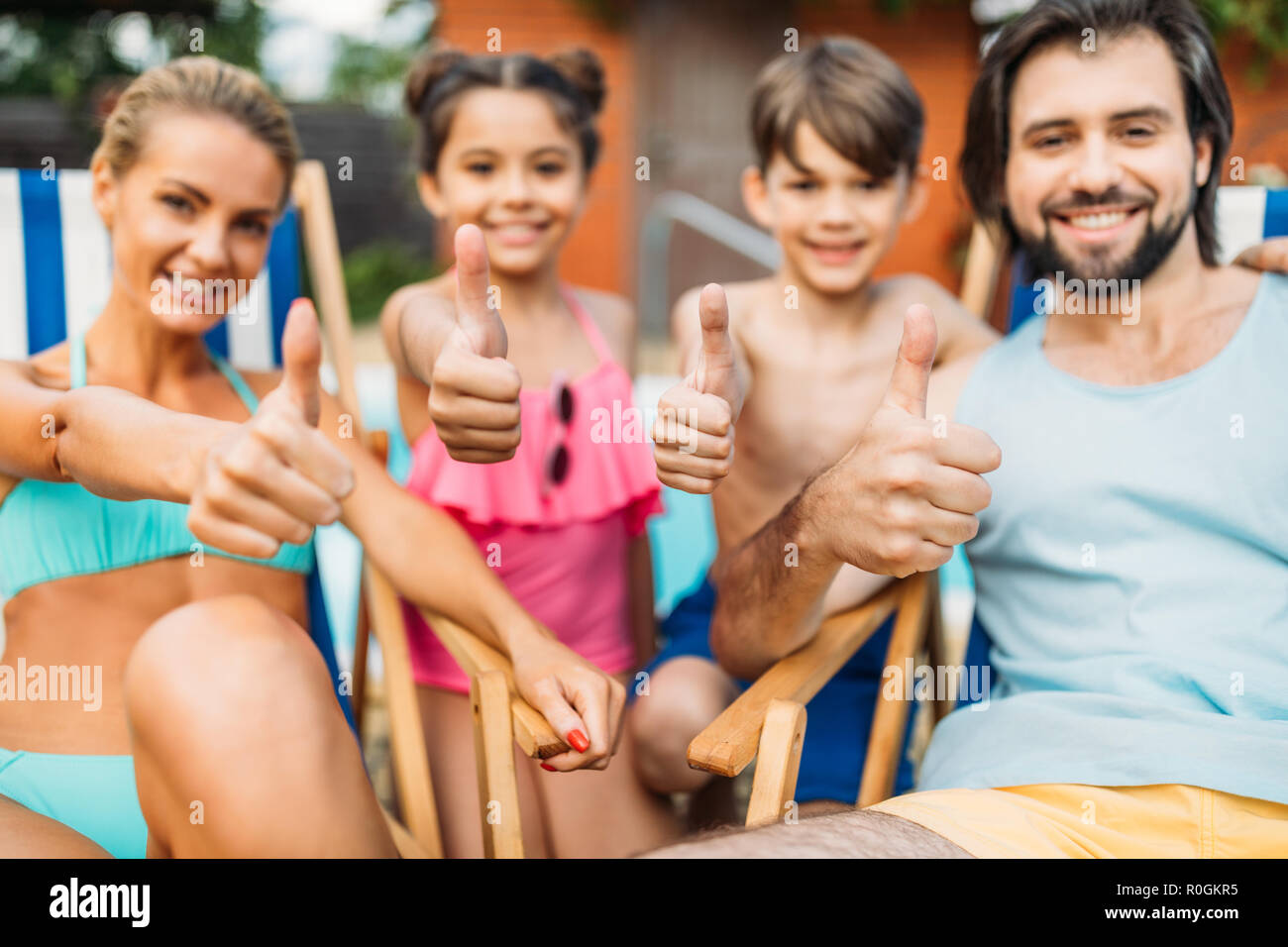 selective focus of family showing thumbs up while spending time near swimming pool on summer day - Stock Image
