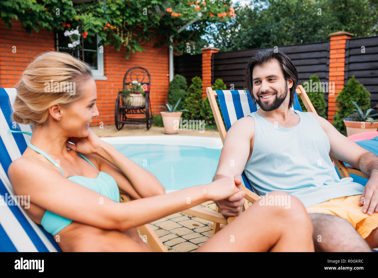 couple on beach chairs holding hands while spending time near swimming pool on backyard on summer day - Stock Image