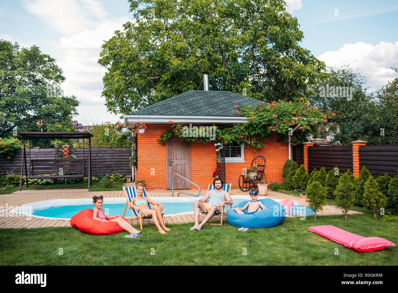 family resting on beach chairs and bean chairs near swimming pool at countryside backyard on summer day - Stock Image