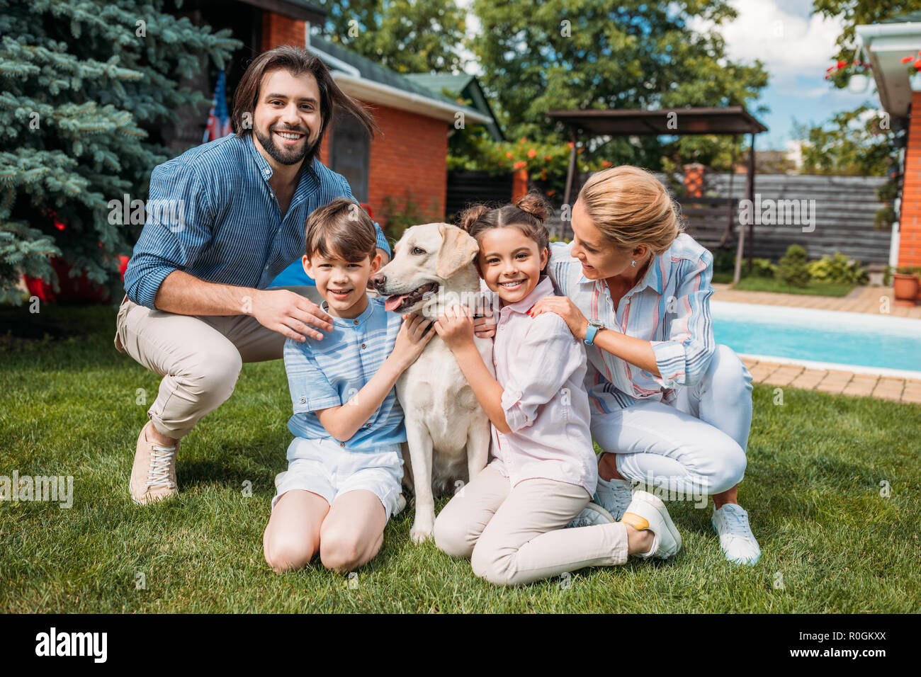 happy family with labrador dog looking at camera while spending time on backyard of country house on summer day - Stock Image
